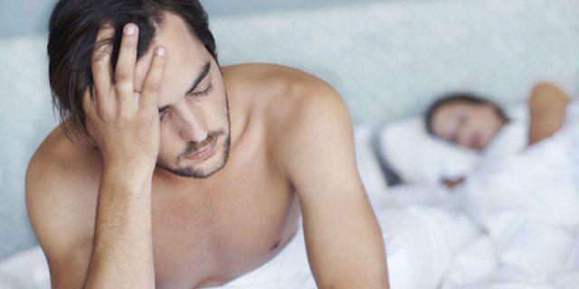 Мужчина сидит на краю постели