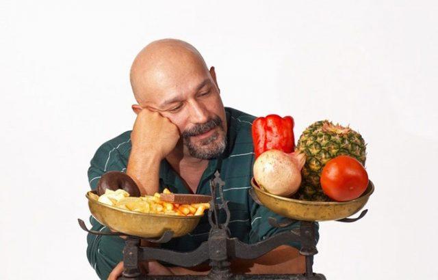 Мужчина выбирает между вредной и полезной едой