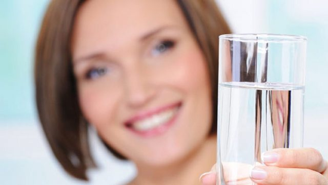 Женщина держит стакан с водой