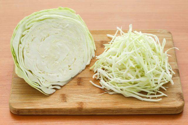 Половина вилка капусты справа и нашинкованный овощ слева