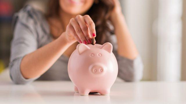 Женщина бросает монету в свинью-копилку