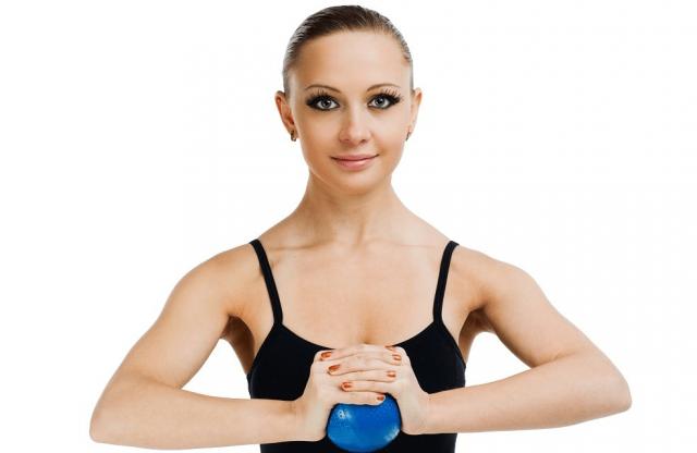 Женщина делает упражнение для груди