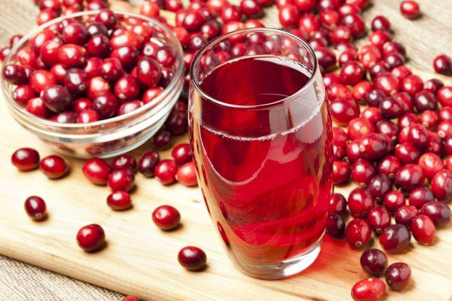 Клюквенный сок в стакане и ягоды на столе