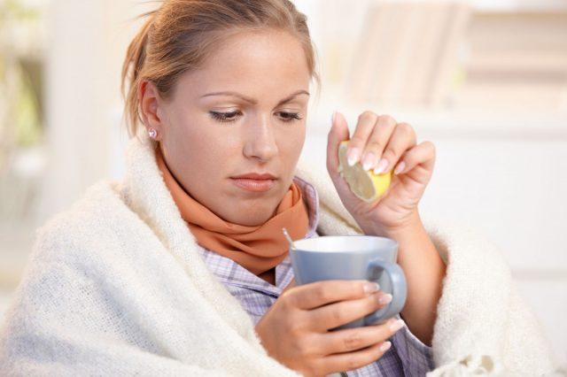 Девушка пьёт чай с лимоном