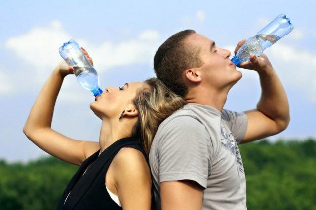 Женщина и мужчина пьют воду из бутылок