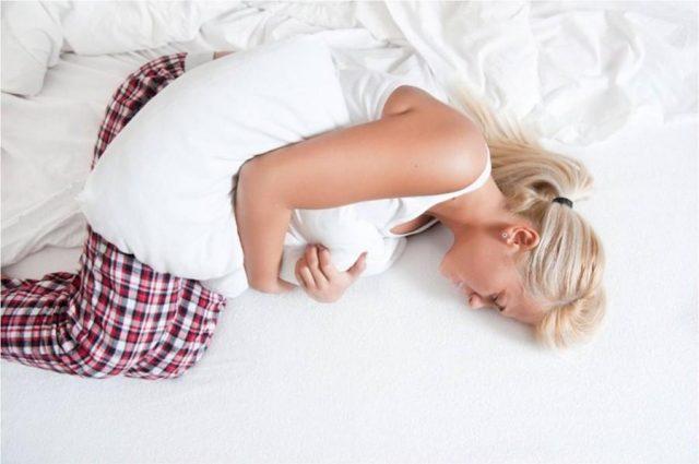 Женщина свернулась на кровати, прижав к животу подушку