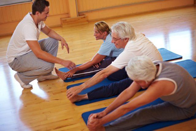 Пожилые люди занимаются гимнастикой с тренером