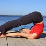 девушка выполняет упражнение «Плуг» возле реки