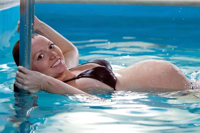Беременная девушка плавает в бассейне