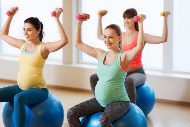 Гимнастика для беременных: три женщины на фитболах и с гантелями на групповом занятии