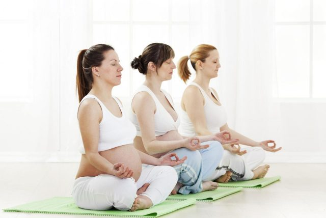 Три женщины на групповом занятии йогой для беременных