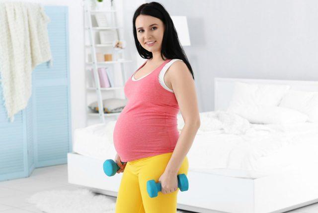 Беременная девушка с маленькими гантелями в своей спальне