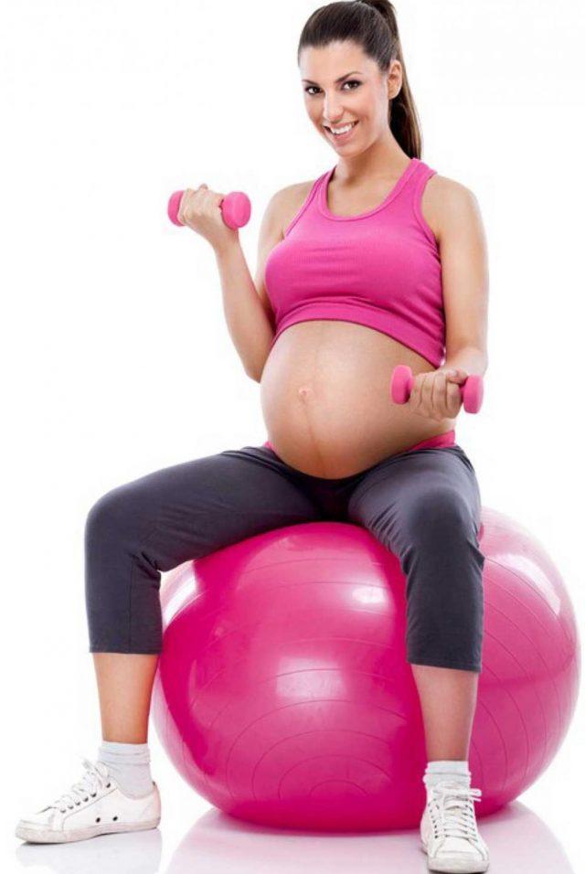 Беременная женщина на фитболе и с гантелями