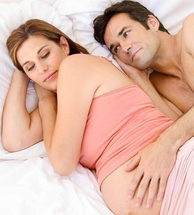 Беременная женщина спит рядом с мужем