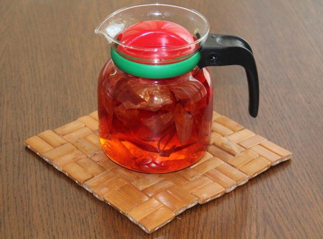 На столе стоит прозрачный чайник с отваром из луковой шелухи