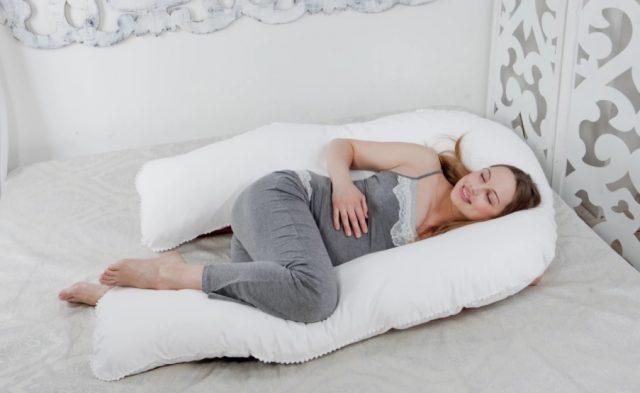 Беременная женщина спит со специальной подушкой