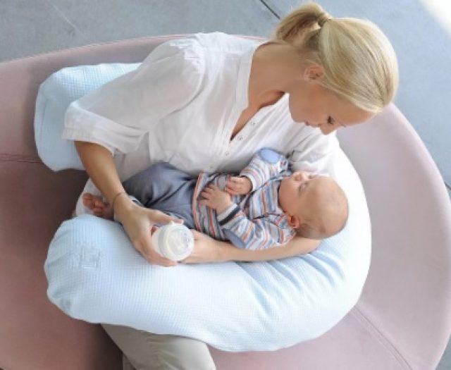 Женщина кормит грудью ребенка на подушке