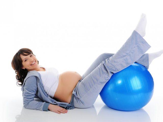 беременная держит ноги на фитболе