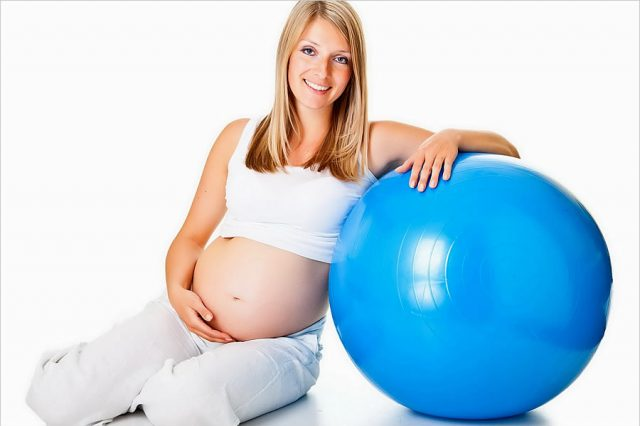 беременная женщина опирается на фитбол
