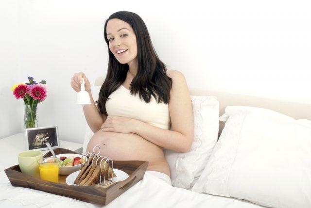 Беременная женщина сидит в постели с подносом еды