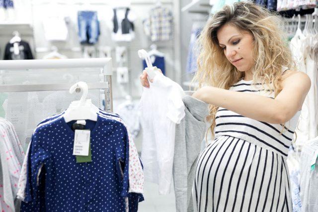 Беременная женщина в магазине выбирает одежду