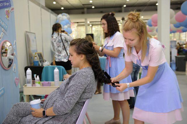 Беременная женщина сидит в парикмахерской