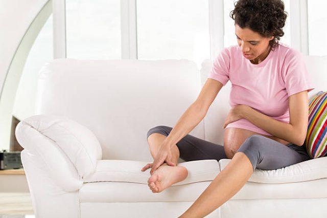 Беременная женщина сидит на диване, взявшись за ногу