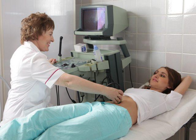 Врач-сонолог проводит абдоминальное УЗИ беременной женщине