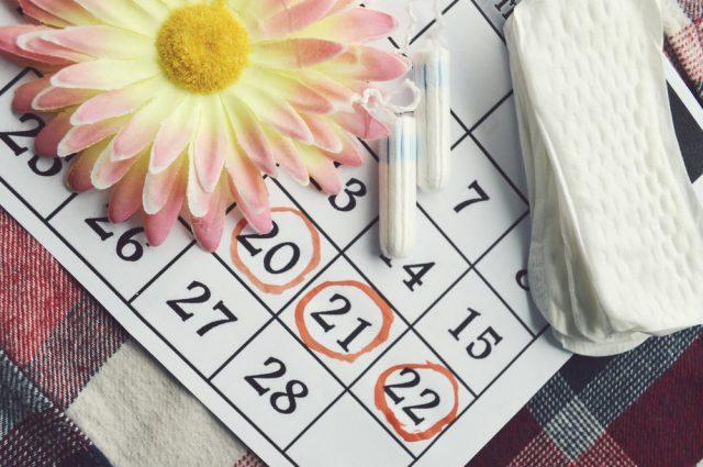 На календаре лежат ромашка, прокладки и тампоны