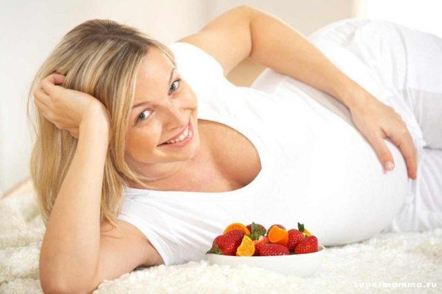 Беременная женщина ест ягоды