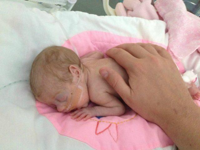 Малыш спит на животе, на нём человеческая рука