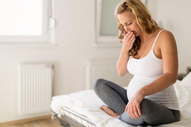 Беременная жнщина сидит на кровати, прикрыв рот рукой