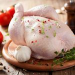 Свежая тушка курицы на разделочной доске