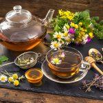 Травяной чай в прозрачных чайнике и кружке с блюдцем