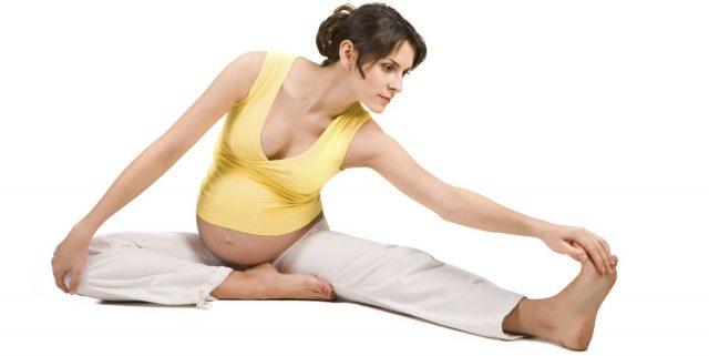 Беременная женщина выполняет гимнастическое упражнение