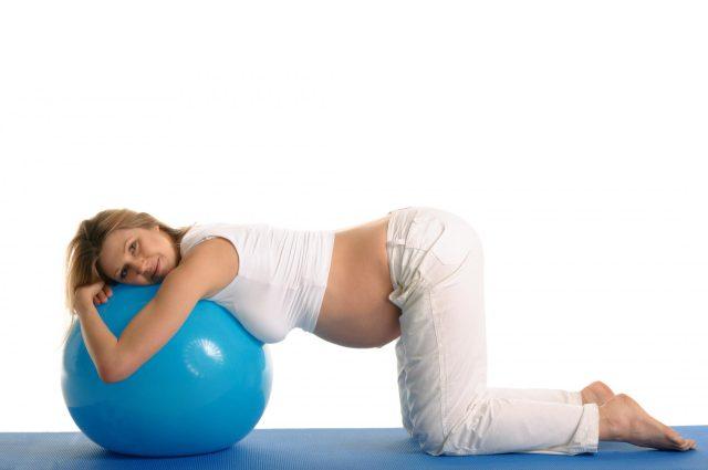 Беременная девушка обхватила руками фитбол