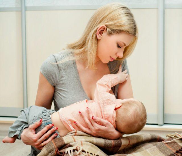 Девушка кормит ребёнка грудью