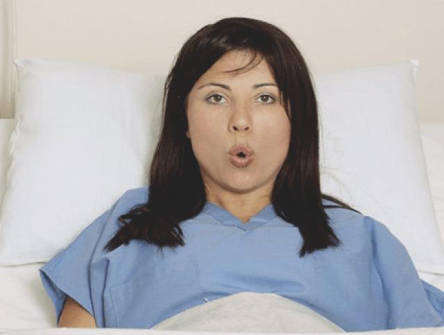 Женщина выдыхает, лёжа в постели