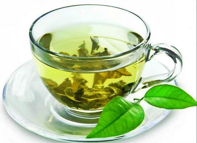 Зелёный чай в прозрачной чашке, стоящей на блюдце