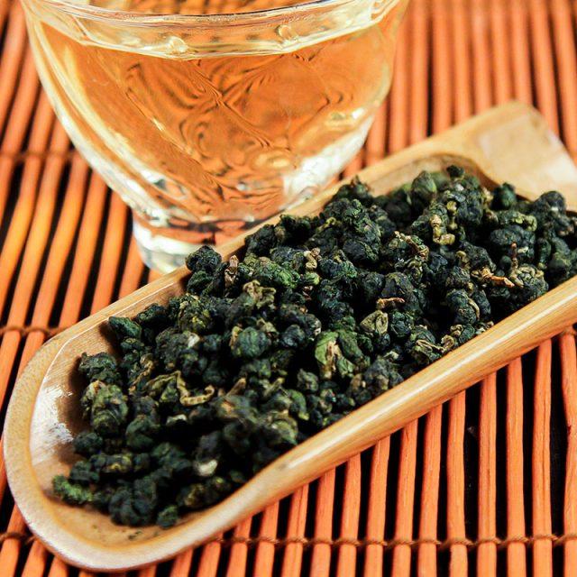 Стакан с напитком и деревянная лопатка с чайными листьями