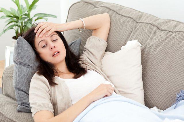 Беременная женщина лежит и держится за голову