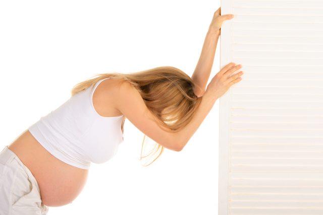 Беременная женщина держится за дверь