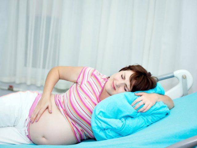 Беременная женщина лежит на боку и держится за живот