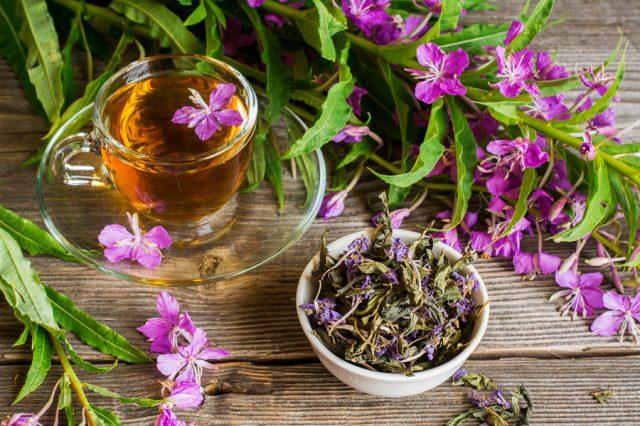 Чай в прозрачной кружке с блюдцем рядом с пиалой с чайными листьями