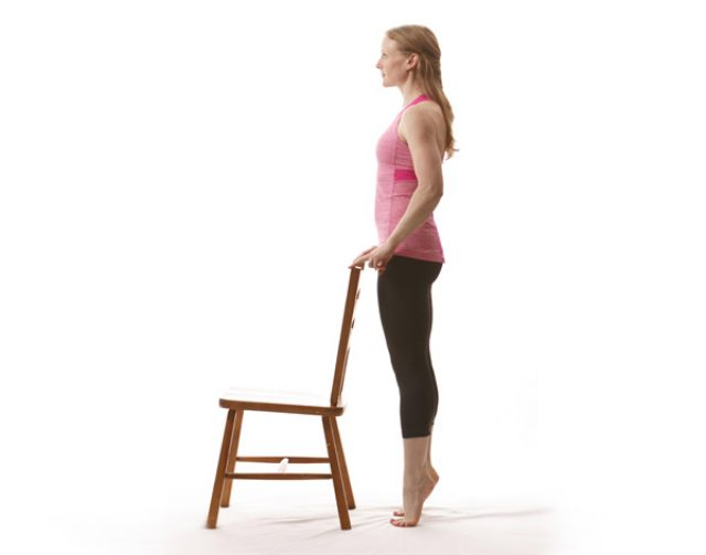 Женщина выполняет подъём на носочки с опорой на стул