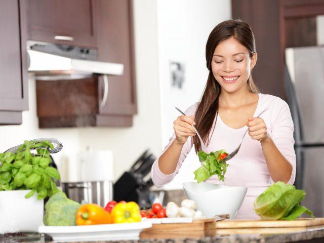 Девушка готовит салат на кухне