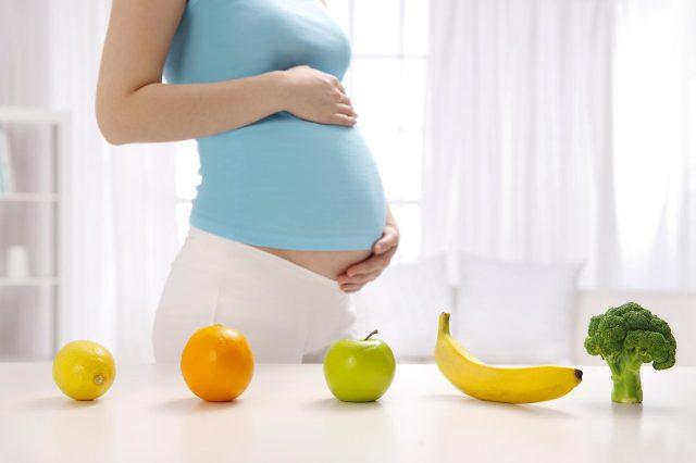 Фрукты и брокколи лежат на столе рядом со стоящей беременной