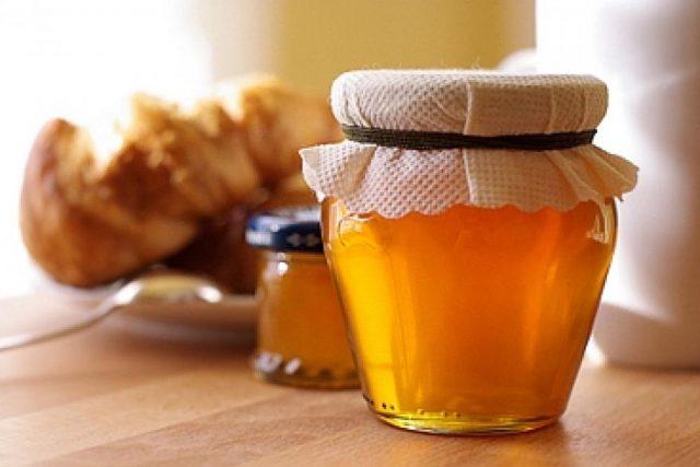 Мёд в стеклянной банке на столе