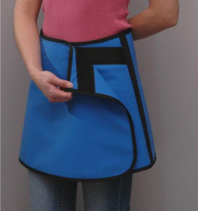 Женщина надевает защитный фартук от облучения перед проведением флюорографии
