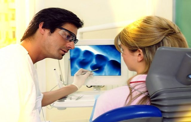 Женщина и врач смотрят на фотографию зубов